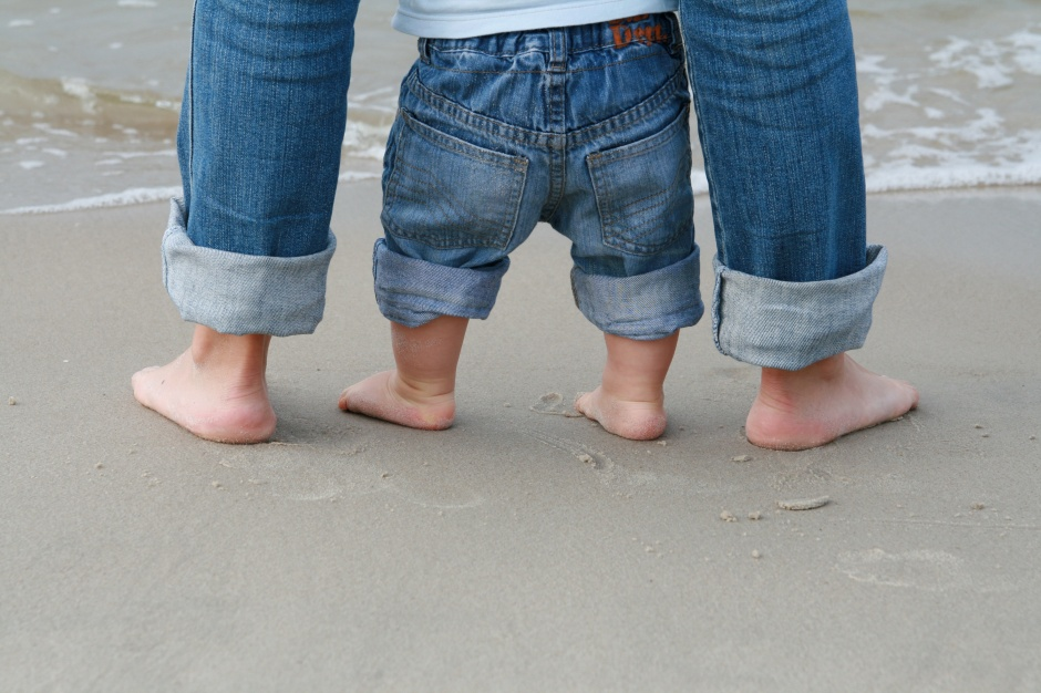 Mother and son bare feet on sandy beach.