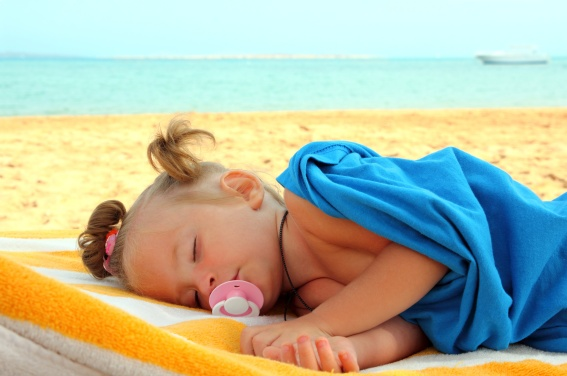 Toddler girl asleep at the beach