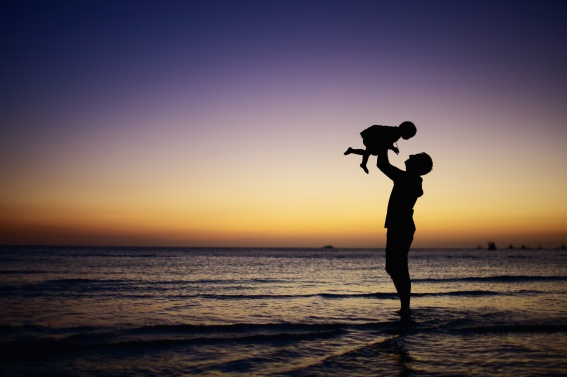 Silhouette of adult holding baby up at the ocean
