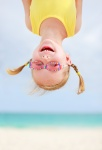 Little girl upside down with ocean background