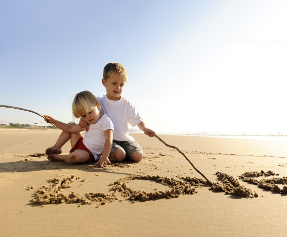 Kids at the ocean, word love written in the sand