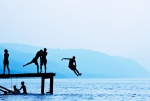 Silhouette photography of kids jumping off a dock at a lake