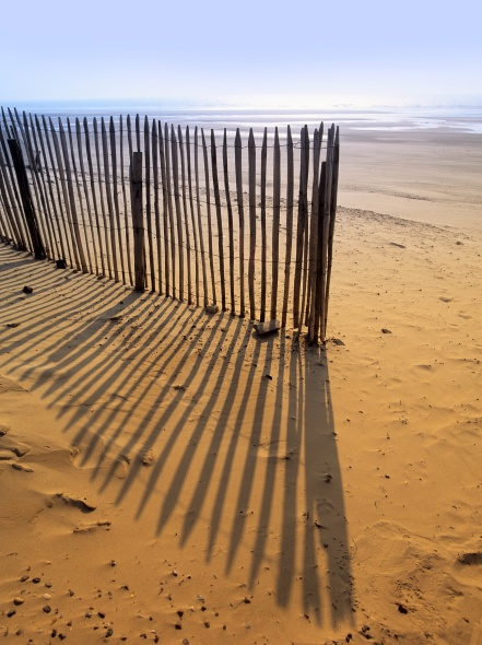 Interesting shadows from fence on beach