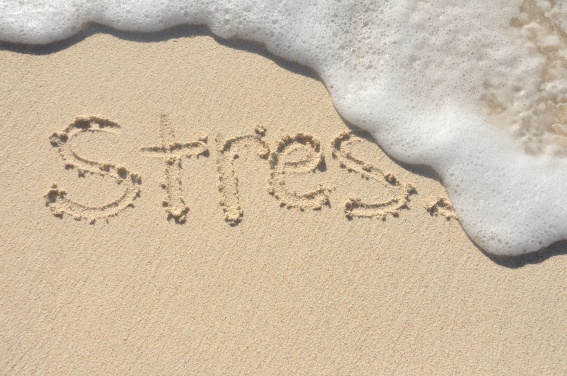 Creative beach photo word stress written in sand