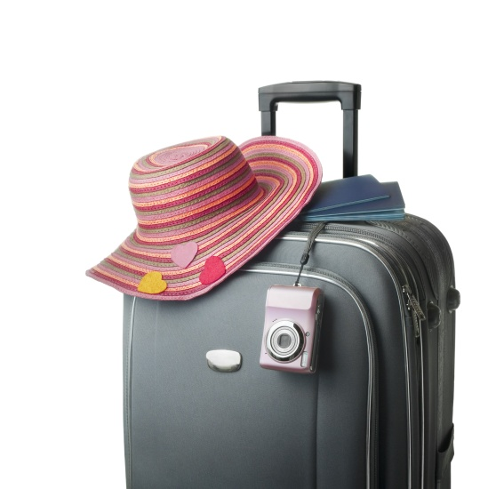 Luggage with camera, passports and woman's hat
