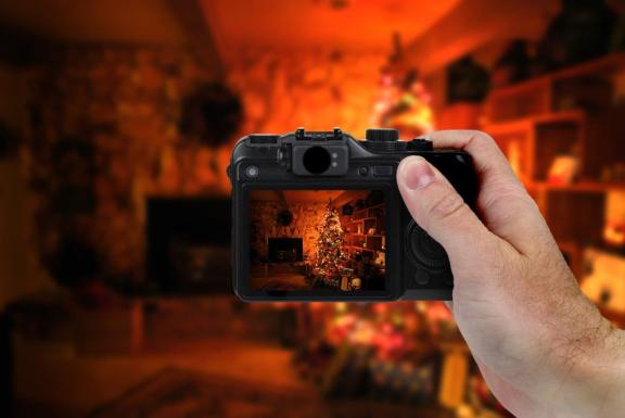 Man with camera looking through viewfinder at Christmas tree and living room fireplace