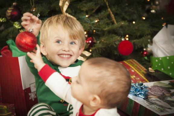 Excited child with younger sibling holding Christmas decoration in front of tree