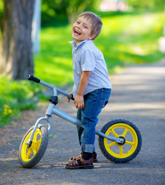 Smiling child sitting on a bike