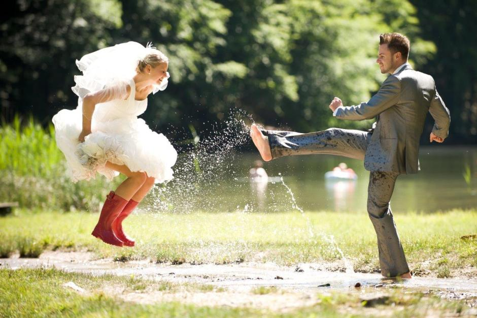 Trash the Dress Wedding Photo Bride in Red Rain Boots Jumping in Mud Puddle with Groom
