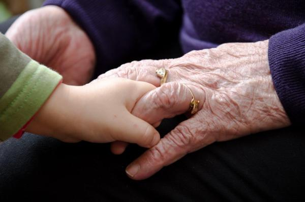 Baby holding hands with an elderly woman