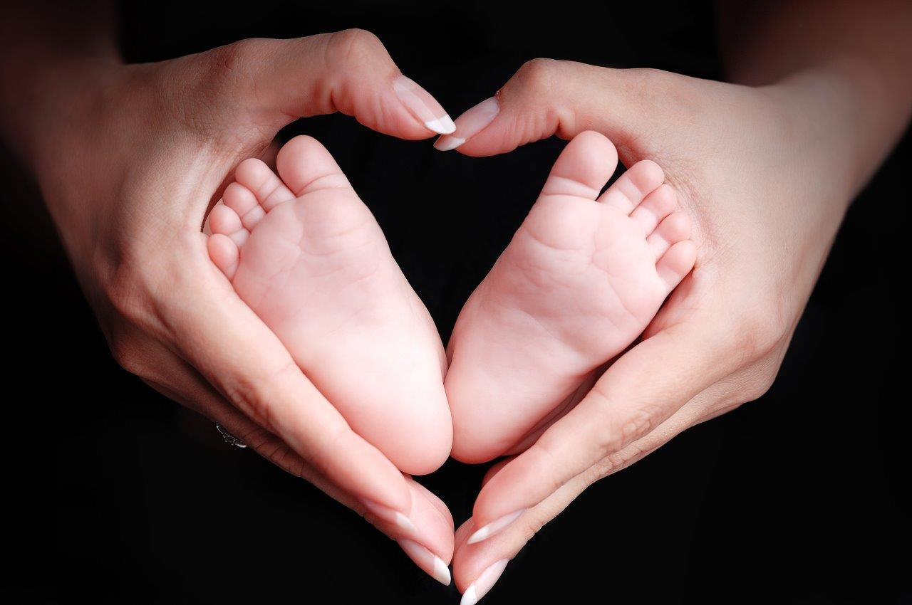 Baby Feet Framed in Parents Heart-Shaped Hands