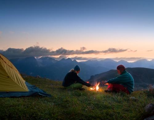 Couple by Fire Camping on Mountains