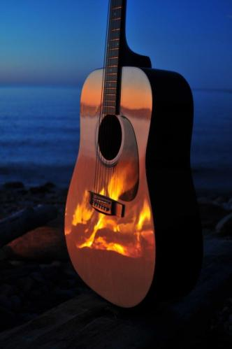 Guitar on Beach with Campfire Light Reflection