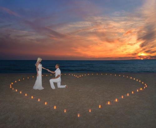 Man Proposing to Woman on Beach by Candlelight and Sunset