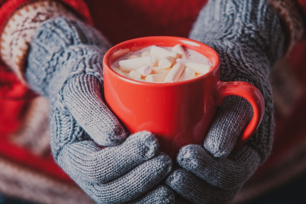 Warm, Knitted Gloves Holding a Mug of Hot Cocoa and Marshmallows