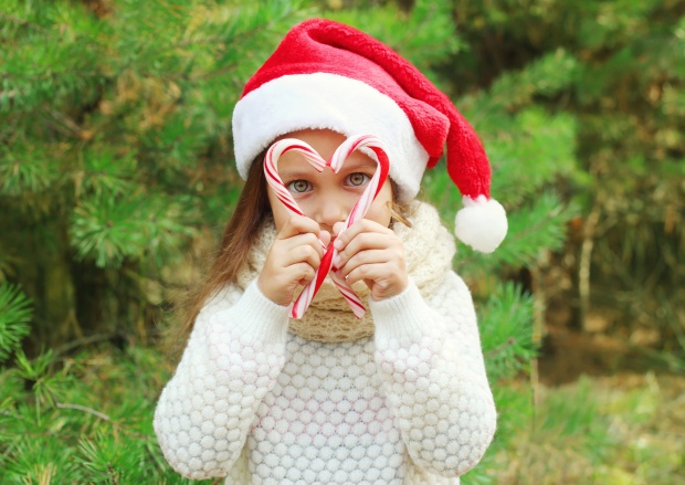 Little Girl Wearing a Santa Hat Framing Her Eyes with Candy Canes