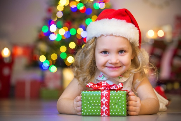 Little Girl with Christmas Gift in Front of Tree with Bokeh Lights