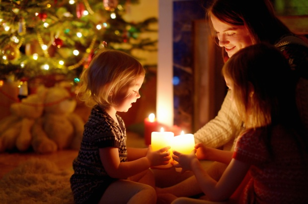 Woman and Two Young Children Holding Candles in Front of Christmas Tree and Fireplace