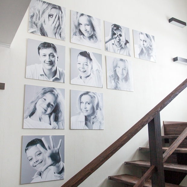 Black and white family portraits displayed in a stairway